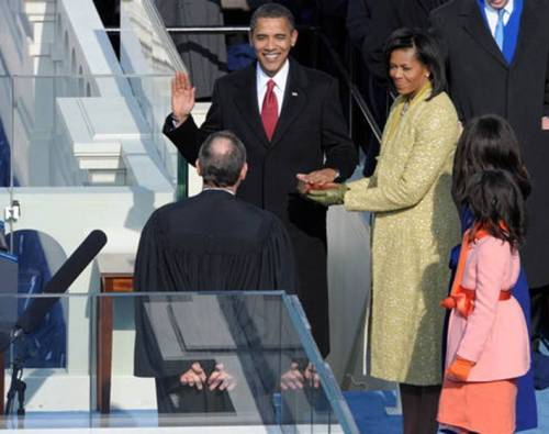 Barack Obama swears in as Michelle Obama and daughters Sasha and Malia look on