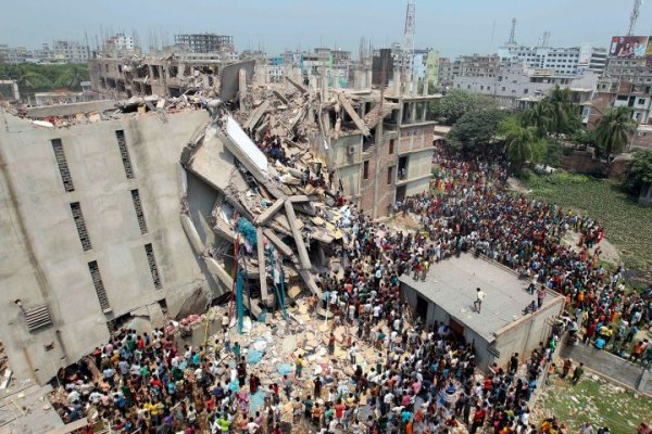 People and rescuers gather after an eight-story building housing several garment factories collapsed in Savar, near Dhaka, Bangladesh, April 24, 2013. Workers in the building said that because it had developed such severe cracks the day before, it had been reported on local news channels. Photo credit: A.M. Ahad/AP