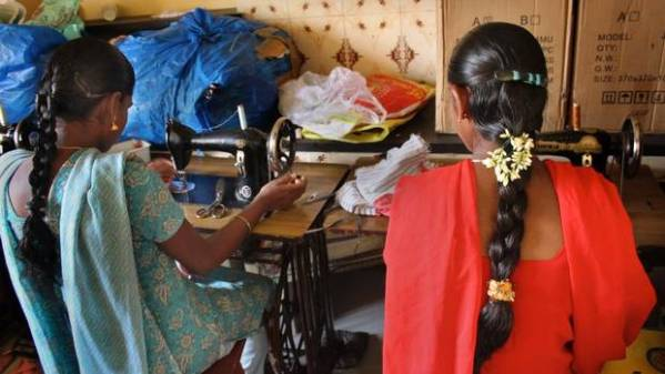 Former bonded textile worker Vasandi, at left in blue, with a friend being trained in tailoring by a group called Rights, Education and Development in Satyamangalam. (Stephanie Nolen, The Globe and Mail)